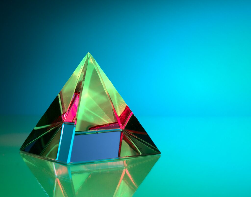 Green and pink crystal prism reflecting a computer screen to illustrate the many layers of IT security.
